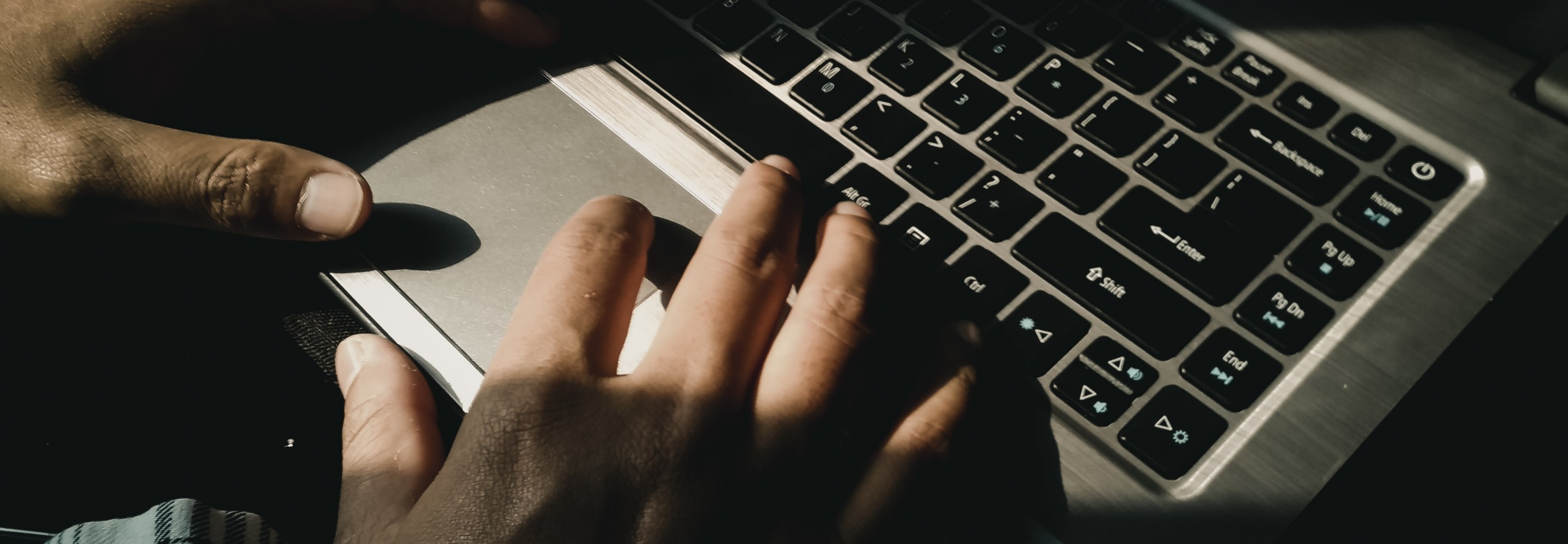 Photo of hands typing on a laptop; Photo by Yudi Indrawan on Unsplash