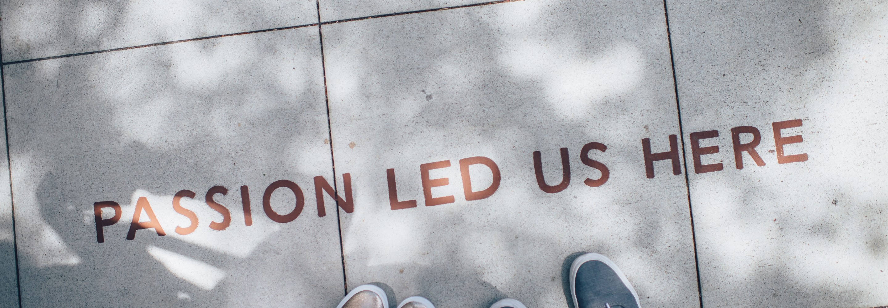 "Photo of two people standing on a sidewalk with the words ""Passion Led Us Here"" painted on; Photo from Ian Schneider on Unsplash"