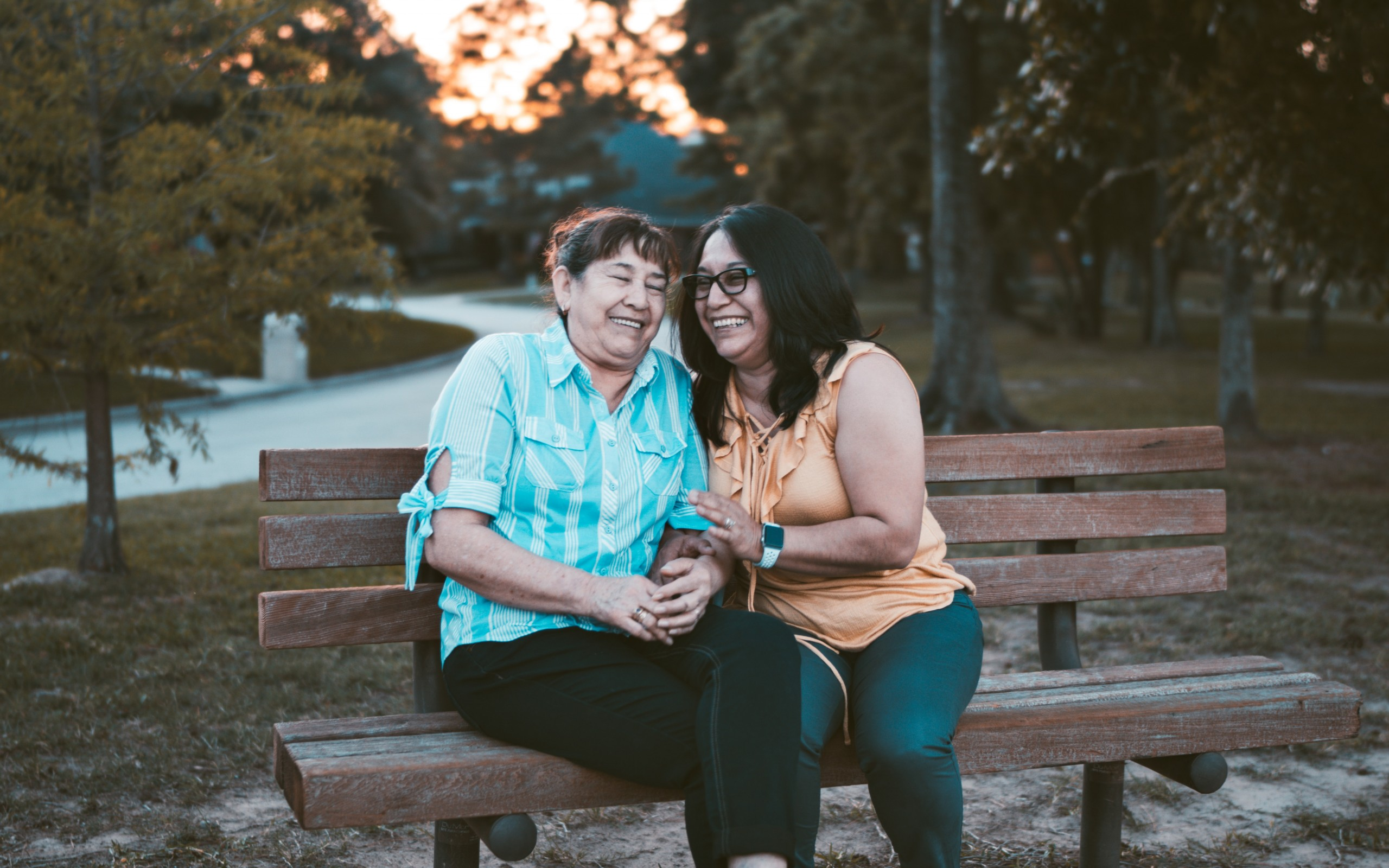 Two woman sitting on a bench smiling