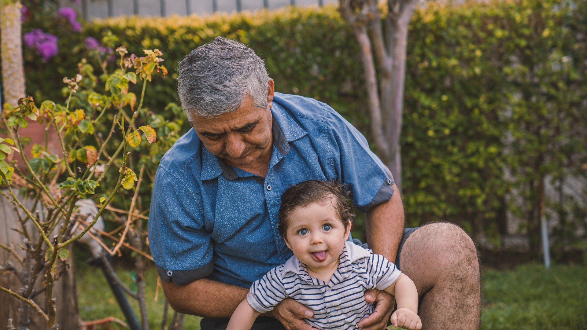 Grandfather wearing a blue shirt hold his grandchild making a silly face