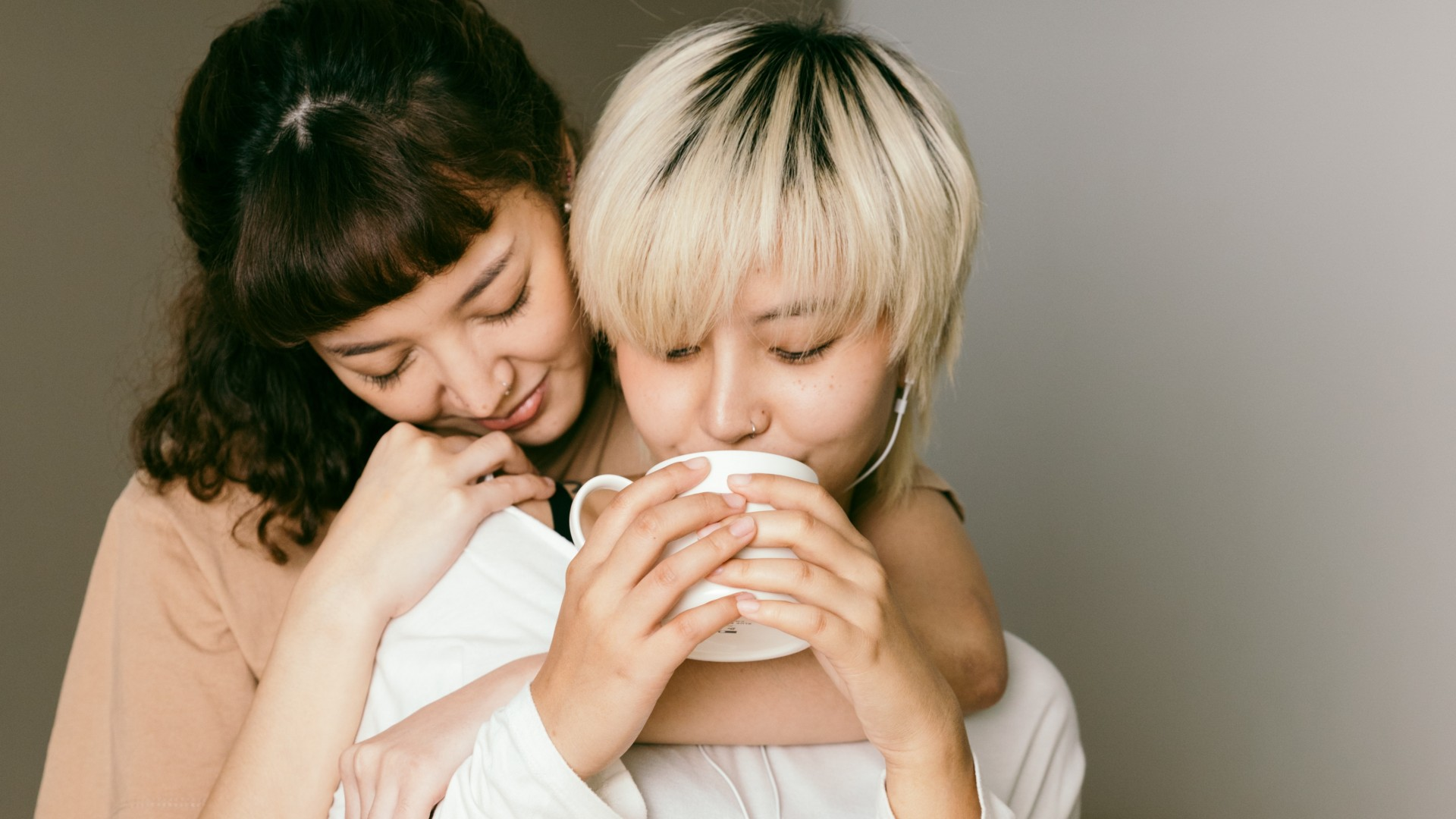 Women hugging while drinking coffee; Photo by Ketut Subiyanto on Pexels