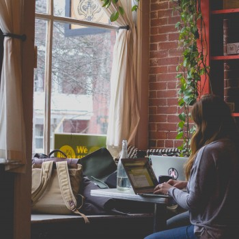 Photo of woman typing on a computer. She sits at a desk in front of a bright window in a cozy room.Photo by Bonnie Kittle on Unsplash