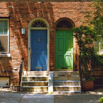 Photo of two rowhomes. One door is painted bright green and one is painted bright blue.  Photo by Tyler Finck on Unsplash